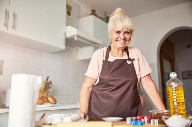 Amable mujer mayor sonriendo en su cocina