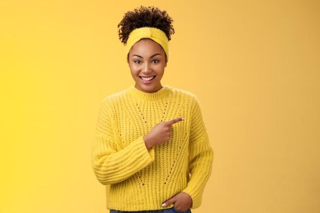 Amable ougoing relajada mujer afroamericana apuntando casualmente a la derecha durante la conversación discutiendo el reciente café nuevo abierto promociones increíbles descuentos de pie felizmente fondo amarillo. copia espacio