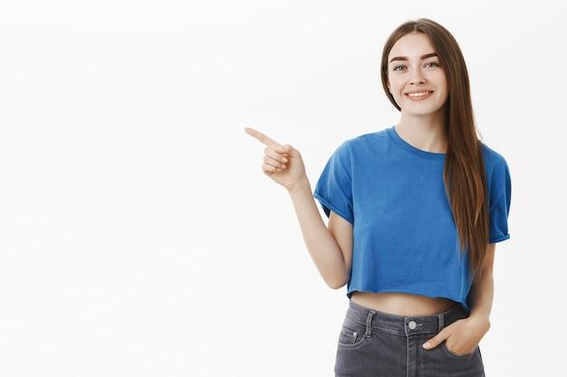 Amable saliente hermosa joven morena en camiseta azul con la mano en el bolsillo de los pantalones vaqueros apuntando hacia la izquierda y sonriendo lindo y educado como si estuviera mostrando el camino al cliente o promocionando algo