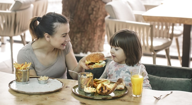 Amando familia. mamá con linda hija comiendo comida rápida en un concepto de cafetería, familia y nutrición