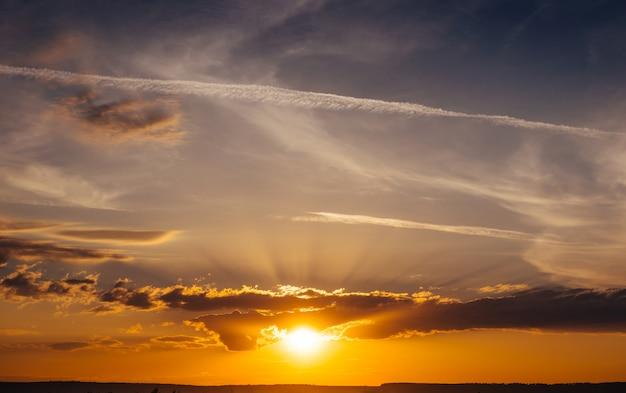 Amanecer al atardecer con nubes, rayos de luz y otros elementos atmosféricos.