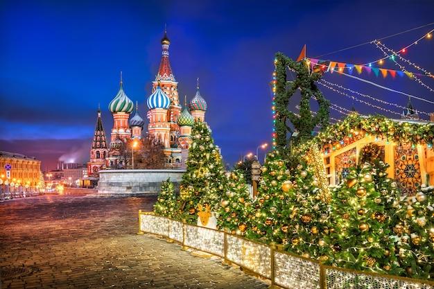 Amanecer azul sobre la catedral de san basilio en la plaza roja de moscú y árboles de navidad en juguetes