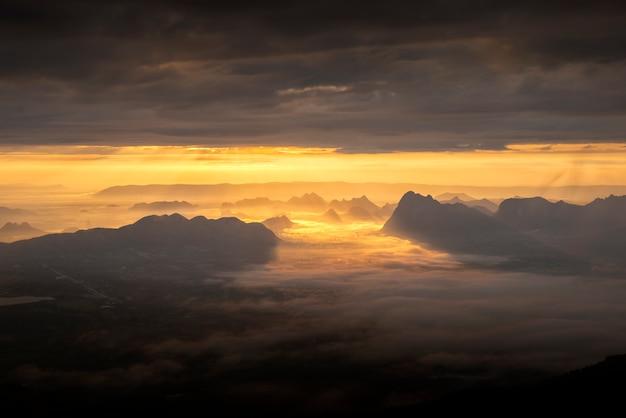 Amanecer de la mañana con la niebla en las montañas