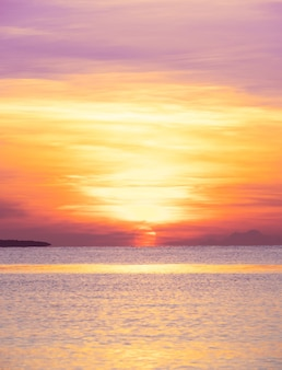 Amanecer de mar tropical con sol bajo el cielo de nubes