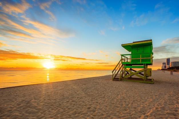 Amanecer de miami south beach con torre de salvavidas y costa con nubes de colores y cielo azul.