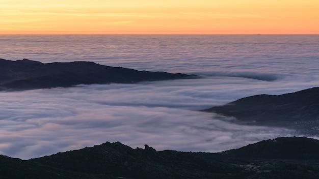 Amanecer sobre la niebla