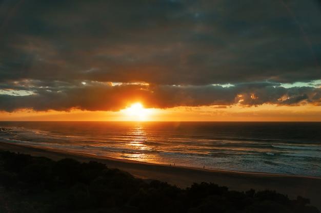 Amanecer temprano en la playa del océano, con siluetas de personas caminando y nubes dramáticas