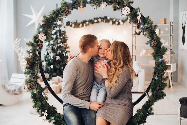 Amante de la familia acurrucarse en el columpio de navidad. árbol de navidad.