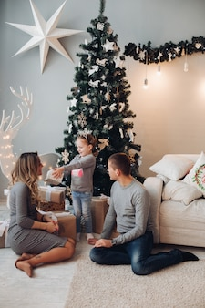 Amante de la familia con la hija en el sofá en navidad.