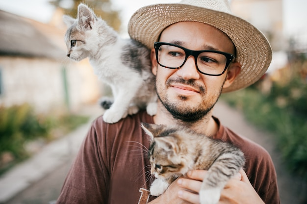 Amante de los gatos. muchacho feliz joven en el sombrero de paja que celebra dos gatitos en la naturaleza.