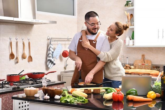 Amante joven pareja asiática cocinando en la cocina haciendo comida sana juntos sintiéndose divertido