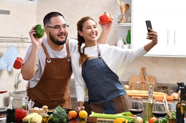 Amante de la joven pareja asiática cocinando en la cocina haciendo comida sana juntos sintiéndose divertidos y usando el teléfono inteligente para tomar selfies