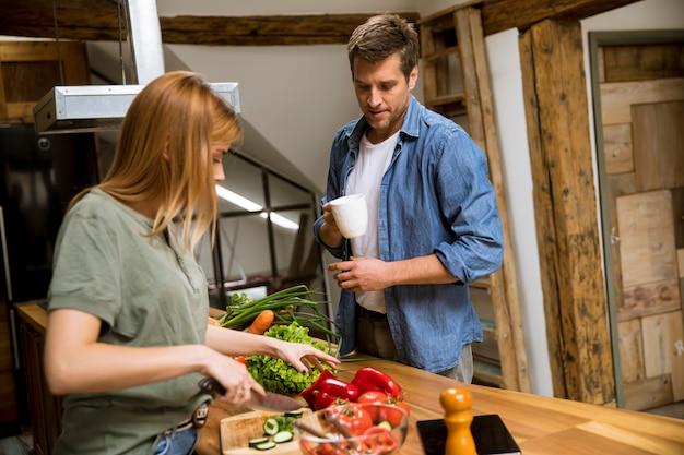 Amante joven pareja cortar verduras juntos en cocina rústica