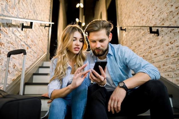 Amante joven pareja en ropa casual con teléfono celular, sentado en las escaleras, en el elegante pasillo del hotel loft