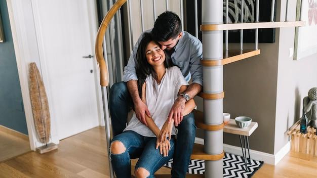Amante joven pareja sentada en la escalera de caracol