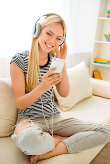 Amante de la música alegre sentado en el sofá con auriculares blancos