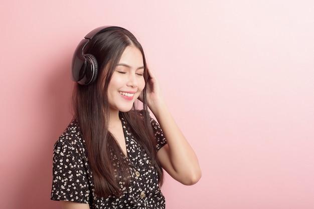 Amante de la música mujer está disfrutando con auriculares sobre fondo rosa