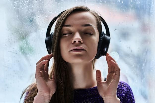 Amante de la música de mujer con los ojos cerrados con auriculares inalámbricos disfruta y escucha un sonido relajante y relajante durante el clima lluvioso de otoño