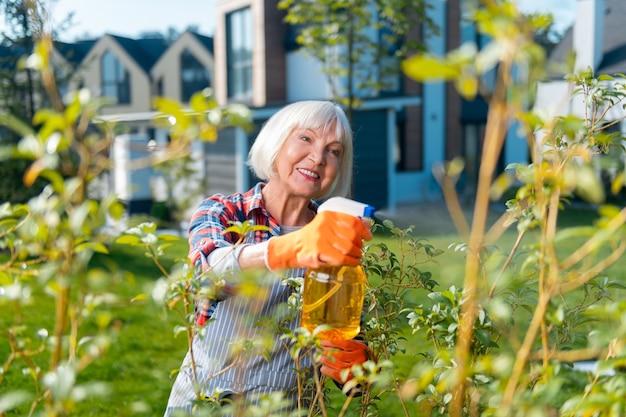 Amante de la naturaleza. amable mujer agradable sonriendo mientras cuida de las plantas