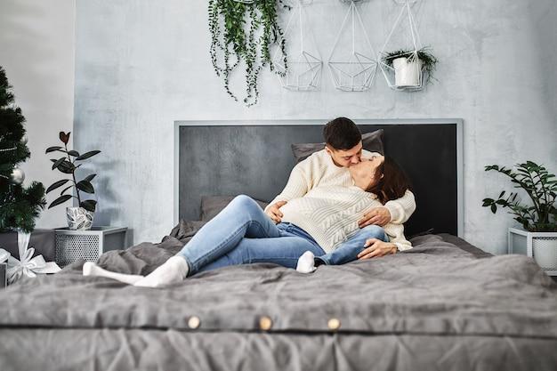Amante pareja embarazada, acuéstese en la cama y mírense. en previsión del bebé, una nueva vida, felicidad y problemas de una familia joven en el nacimiento de un niño.