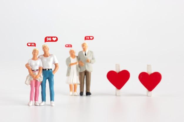 Amante de la pareja en miniatura en jóvenes y ancianos sobre fondo blanco.