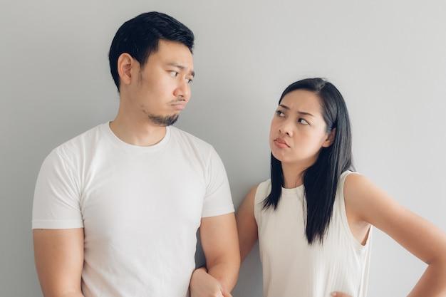 Amante triste de los pares en la camiseta blanca y el fondo gris.