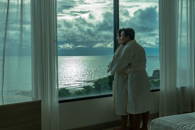 Amantes asiáticos en traje de bata de baño abrazando y visitando la playa del mar al despertarse