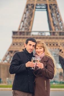 Los amantes beben vino cerca de la torre eiffel en parís. enfoque selectivo.