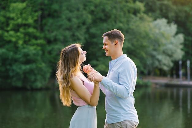 Amantes chico y chica cogidos de la mano y sonriendo en la naturaleza