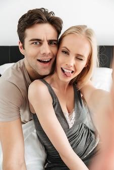 Amantes divertidos y atractivos haciendo selfie y haciendo muecas por la mañana