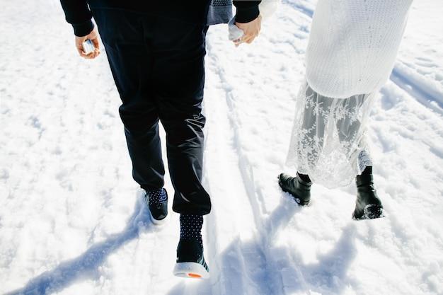 Amantes felices caminan juntos en la nieve