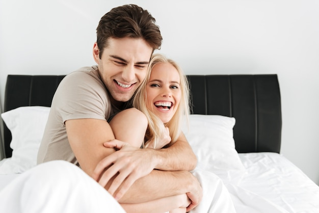 Amantes guapos felices riendo mientras está sentado en la cama