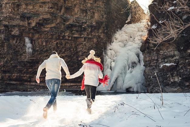 Amantes en invierno en la cascada a pasear