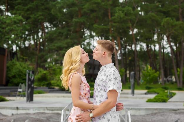 Amantes de la joven pareja besos en parque verde
