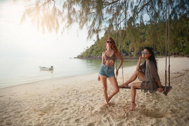 Amantes joven pareja de chicas. en la playa .
