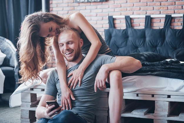 Los amantes jóvenes atractivos tienen una pareja jugando juntos en la cama.