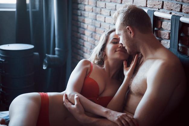 Amantes jóvenes jugando juntos en la cama, vistiendo lencería sexy en una habitación de hotel.