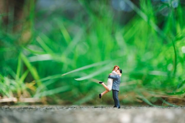 Los amantes de las miniaturas se abrazan en el fondo de la naturaleza verde utilizando como concepto de familia y amor