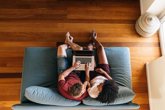 Amantes multiétnicos sentados juntos en el sofá con el portátil