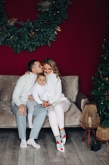 Amantes padres jóvenes sentados en el sofá y besando mientras sostienen a un niño entre ellos