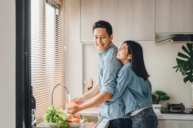 Los amantes de la pareja asiática se abrazan en la cocina mientras cocinan en casa