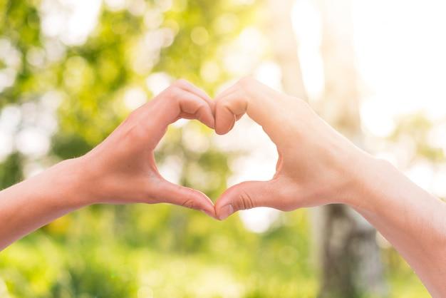 Los amantes que gesticulan el corazón firman con las manos afuera