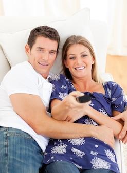 Amantes relajados viendo televisión tumbado en el sofá