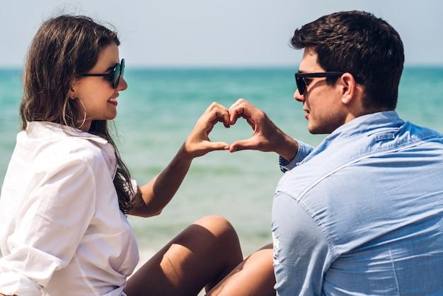 Amantes románticos joven pareja tomados de la mano relajándose juntos en la playa tropical. vacaciones de verano
