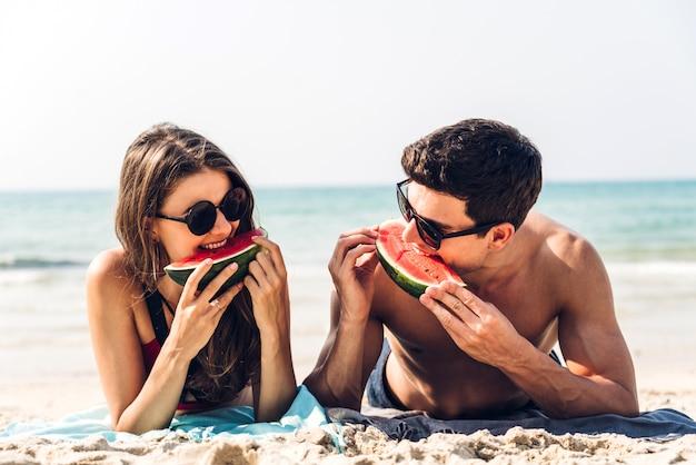 Amantes románticos pareja joven relajante sosteniendo y comiendo una rodaja de sandía