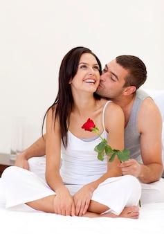 Amantes sentados en la cama con una rosa