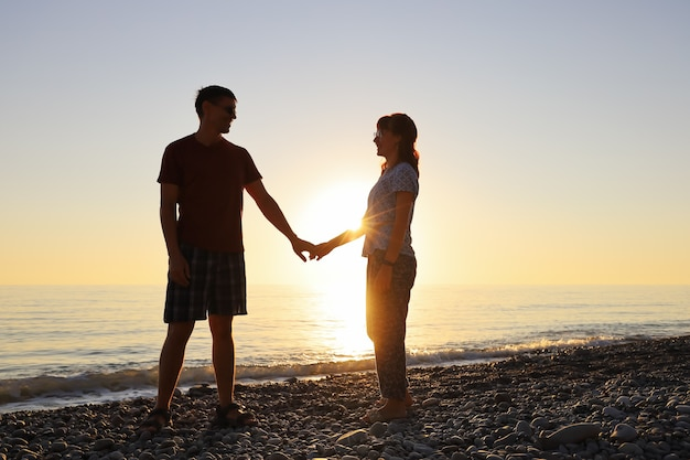 Los amantes sonríen y se miran en los rayos del sol poniente en la orilla del mar