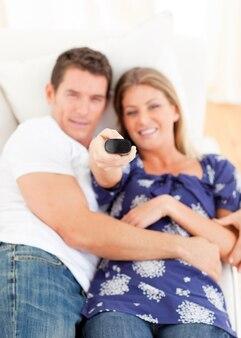 Amantes sonrientes viendo la televisión tumbada en el sofá