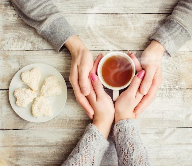 Amantes sosteniendo juntos una taza de té. enfoque selectivo