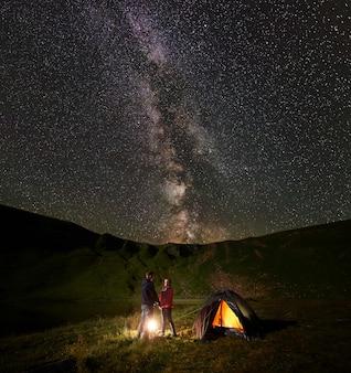 Amantes tomados de la mano mirándose entre ellos quemando fuego cerca de la carpa bajo el cielo estrellado de las montañas y el lago al pie. en el cielo brillante vía láctea